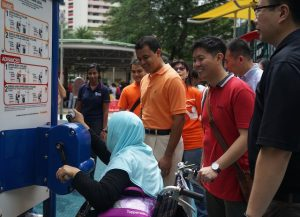 Mr Christopher De Souza interacting with elderly visitors to the SMRT Gh...