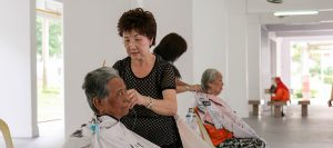 A retired hairdresser, Zhang Yu Lan, offers haircuts to elderly residents for free.