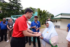 Chan Chun Sing, Secretary-General of National Trade Union Congress (NTUC) offering a token of appreciation to a worker who works in Sentosa, as part of the Young NTUC U Heart initiative.