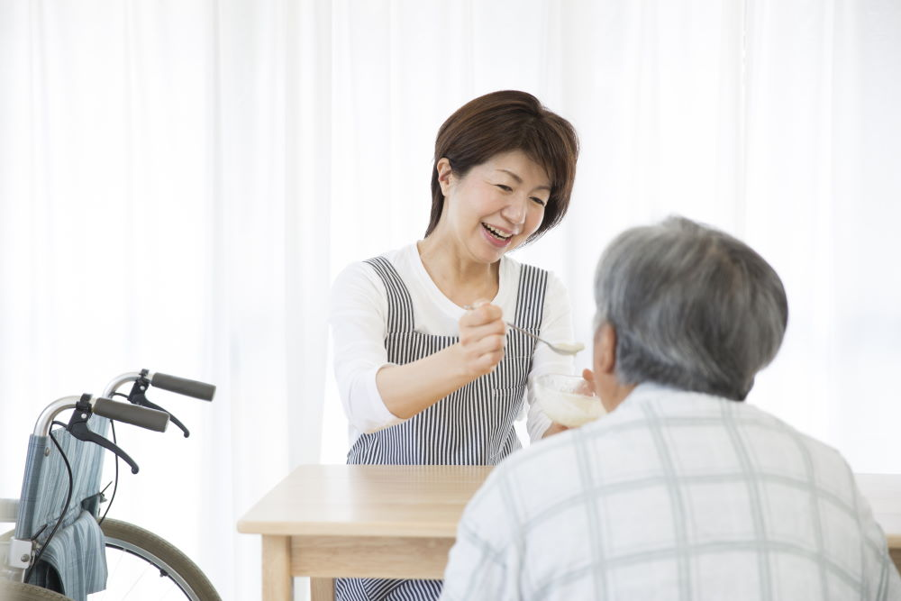 healthcare assistant feeding food to the elderly